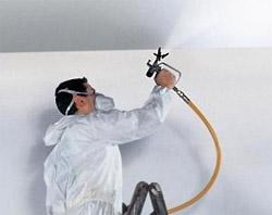 Рабочий красит потолок